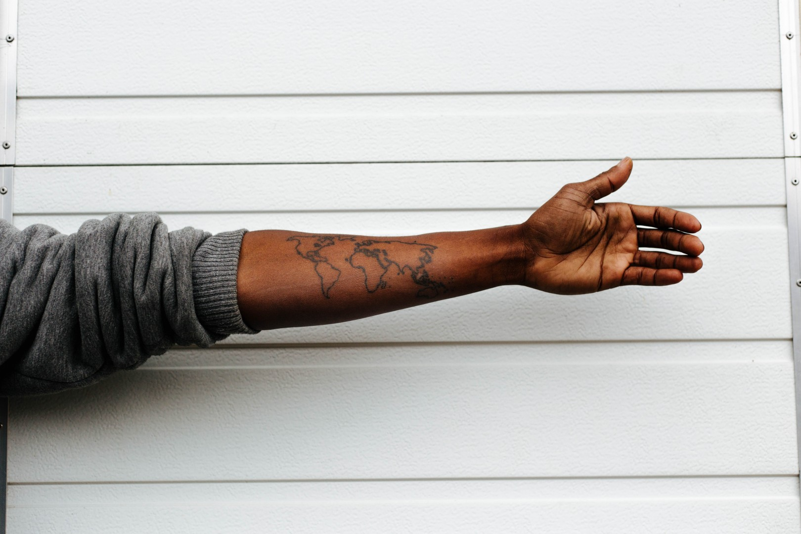 man with arm out world tattoo