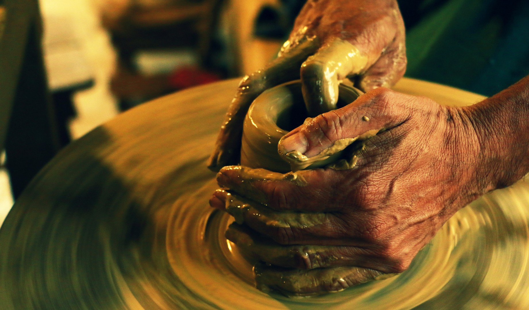 man's hands spinning pottery