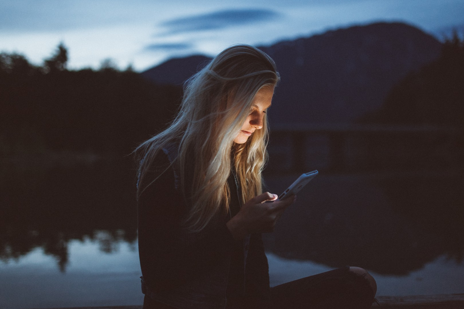 woman looking at phone in nature