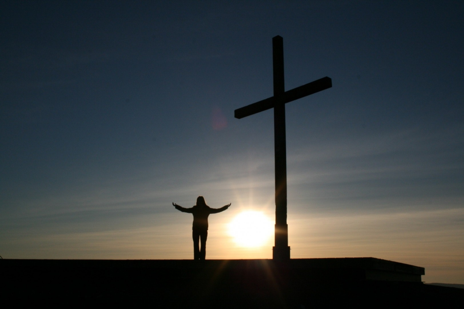 man standing on hill with cross
