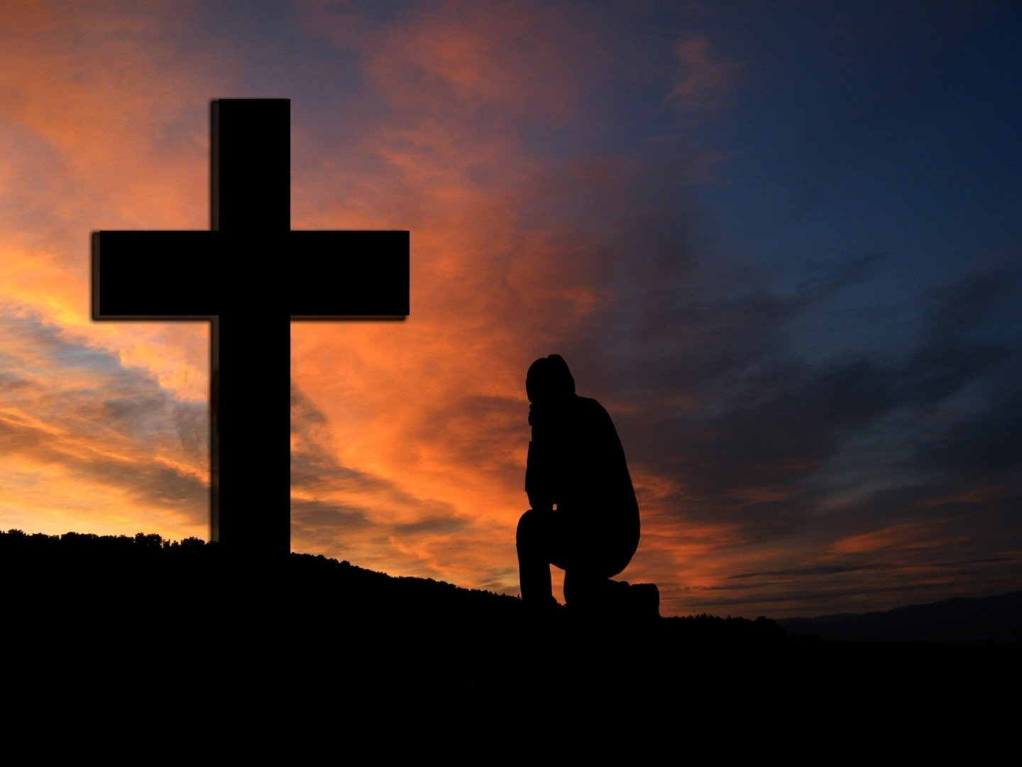 man at cross praying